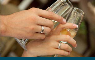 hands with wedding rings toasting wine glasses